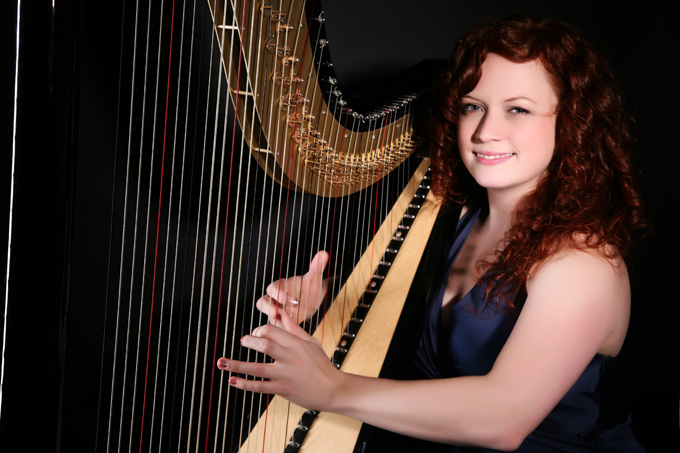 Rachael Gladwin harpist performs on her black and gold harp